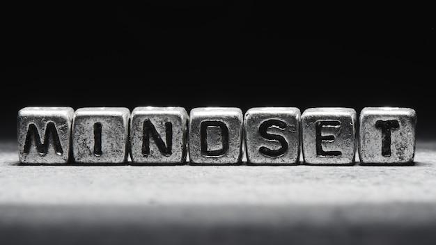 Concept van mentaliteit. de inscriptie op metalen 3d-kubussen geïsoleerd op een zwarte achtergrond, grunge-stijl