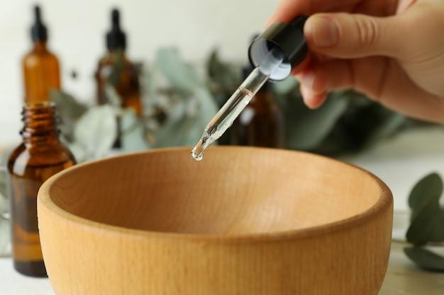 Concept van natuurlijke cosmetica met vrouwelijke hand druipende eucalyptusolie