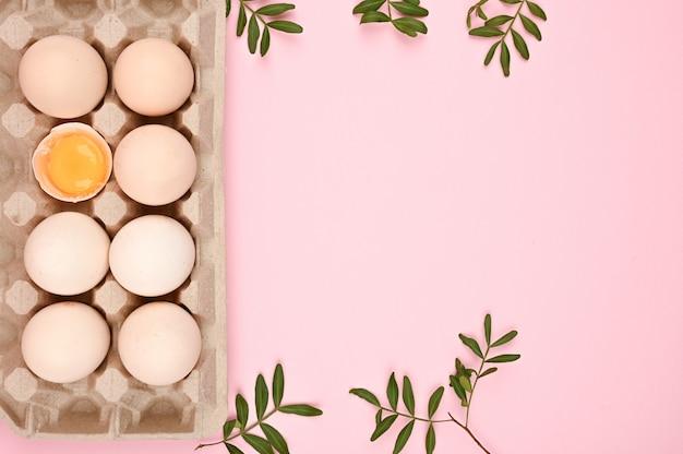 Concept van natuurlijke eieren. een lade van eieren op een witte en roze achtergrond. eco dienblad met testikels. minimalistische trend, bovenaanzicht. eiertray. pasen concept.