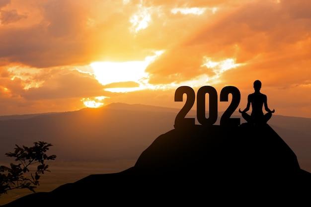 Concept van nieuw silhouet van vrouw yoga op de berg met jaar