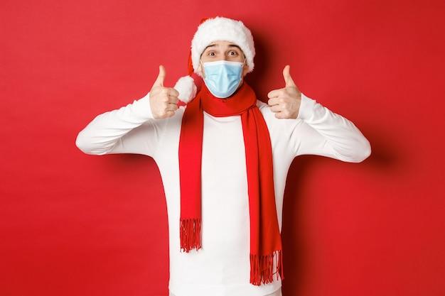 Concept van nieuwjaarscoronavirus en feestdagen vrolijke man die nieuwjaar viert en sociale afstand...