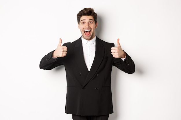 Concept van nieuwjaarsfeest, feest en levensstijl. portret van een verbaasde en blije knappe man in een zwart pak, duimen omhoog, als product, iets goeds goedkeuren, witte achtergrond