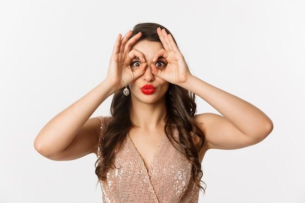 Concept van nieuwjaarsviering en wintervakantie. close-up van mooie brunette vrouw in jurk, rode lippen, hand verrekijker maken en staren naar camera, witte achtergrond.