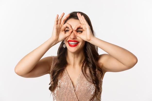 Concept van nieuwjaarsviering en wintervakantie. close-up van mooie brunette vrouw in jurk, rode lippen, hand verrekijker maken en staren naar links, witte achtergrond.