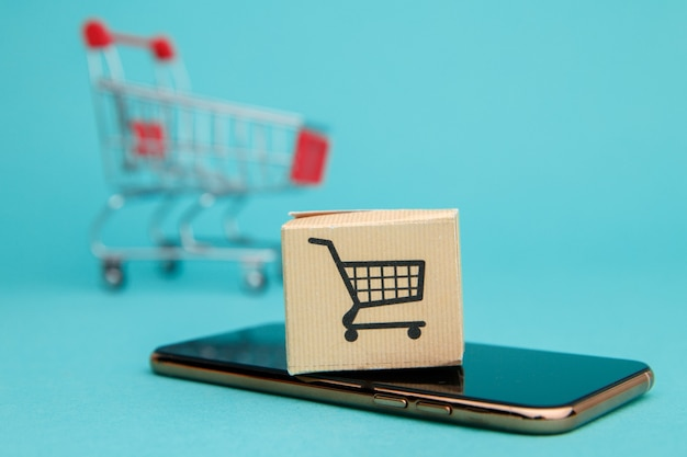 Concept van online winkelen. doos en boodschappentas boven smartphone op blauw