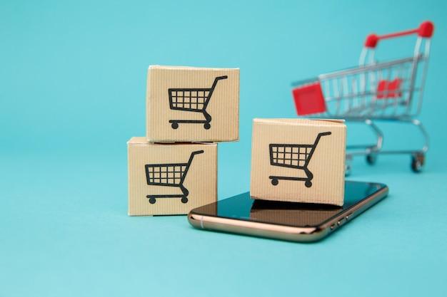 Concept van online winkelen. dozen en boodschappentas boven smartphone op blauw.