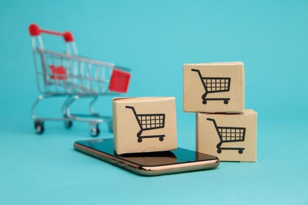 Concept van online winkelen. dozen en winkelwagentje boven smartphone op blauw.