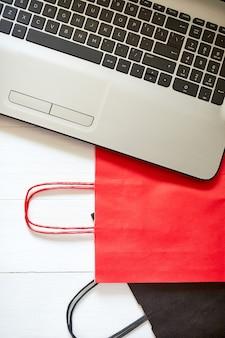 Concept van online winkelen, internetbetaling, e-commerce, mock up, zwarte en rode tas, notitieboekje en hangers op witte achtergrond, verkoopconcept, zwarte vrijdag, plat leggen, kopie ruimte, vrije tekstruimte