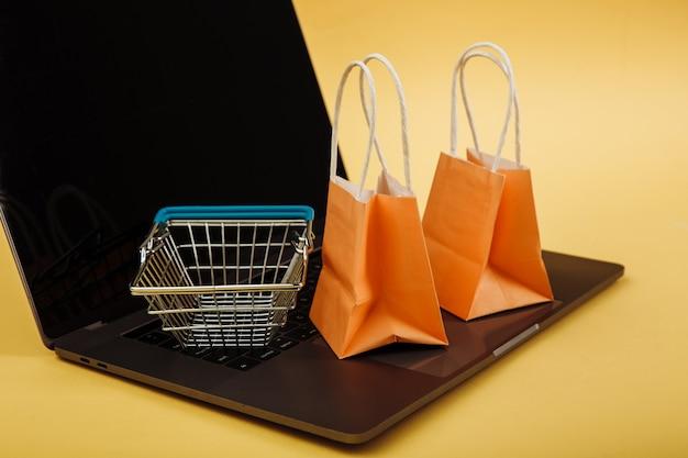 Concept van online winkelen. oranje tassen en winkelwagentje