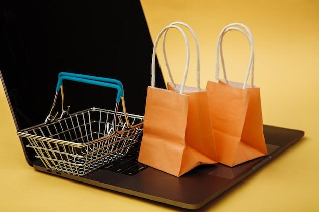 Concept van online winkelen. oranje zakken en boodschappenwagentje op toetsenbord.