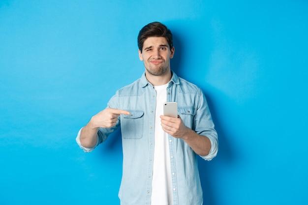 Concept van online winkelen, toepassingen en technologie. sceptische en ontevreden man wijzende vinger naar smartphone en grimassen teleurgesteld, staande over blauwe achtergrond.