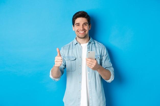 Concept van online winkelen, toepassingen en technologie. tevreden man in vrijetijdskleding glimlachend, duimen opstekend na gebruik van smartphone-app, staande over blauwe achtergrond