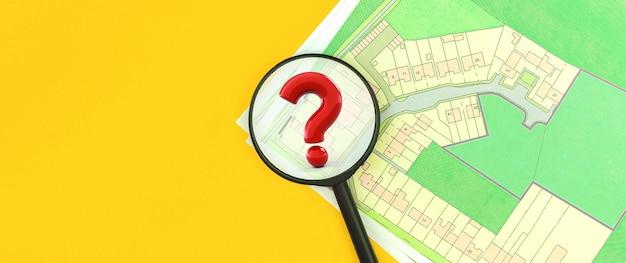 Concept van onroerend goed zoeken, vergrootglas met vraagteken, kadastrale kaart, kies een bouwperceel voor woningbouwfoto