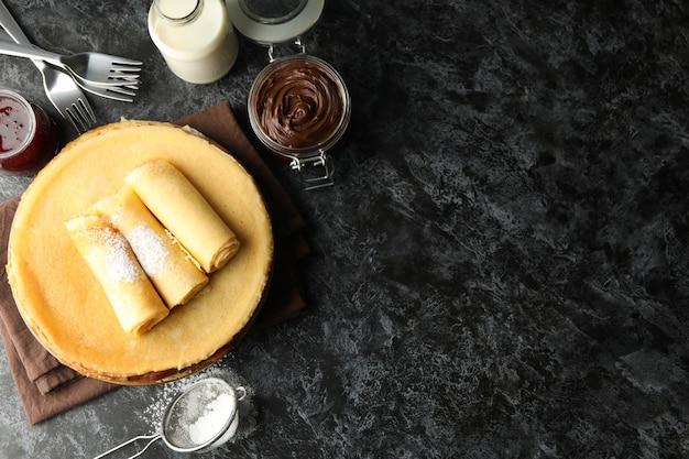 Concept van ontbijt met pannenkoeken met chocopasta op zwarte smokey tafel