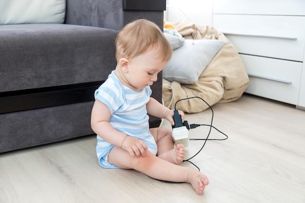Concept van ouder onverantwoordelijkheid. babyjongen zit alleen in de kamer en speelt met elektrische kabels