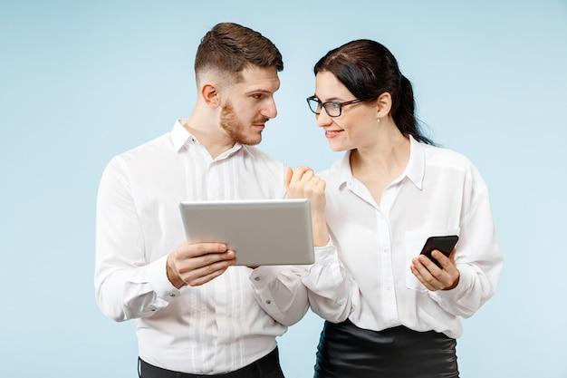 Concept van partnerschap in zaken. jonge emotionele man en vrouw tegen blauwe achtergrond bij studio. menselijke emoties en partnerschap concept