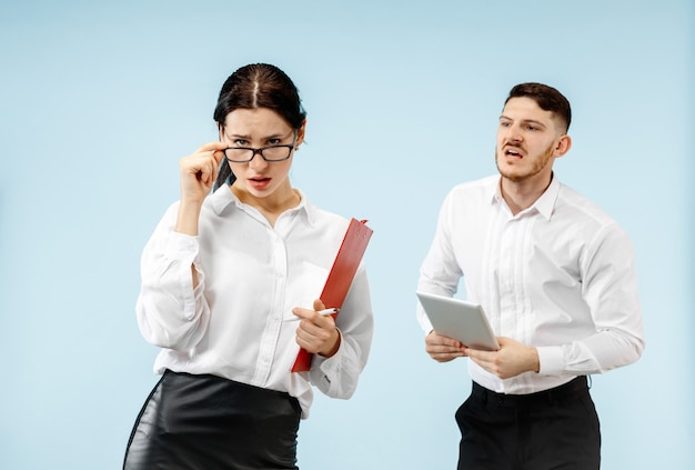 Concept van partnerschap in zaken. jonge emotionele man en vrouw tegen blauwe achtergrond in de studio. menselijke emoties en partnerschap concept