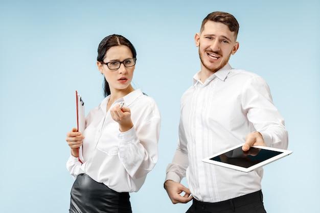 Concept van partnerschap in zaken. jonge emotionele man en vrouw tegen blauwe muur. menselijke emoties en partnerschap concept