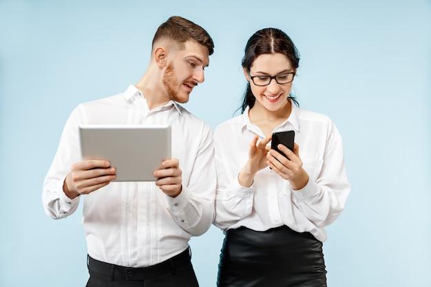 Concept van partnerschap in zaken. jonge gelukkige glimlachende man en vrouw die zich met telefoon en tablet bevinden tegen blauwe achtergrond bij studio