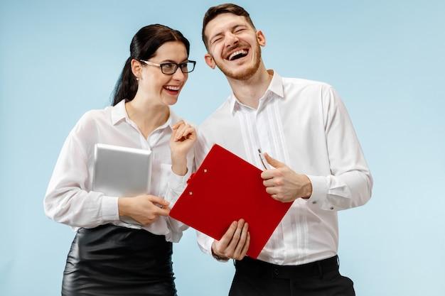 Concept van partnerschap in zaken. jonge gelukkige glimlachende man en vrouw die zich tegen blauwe achtergrond bevinden