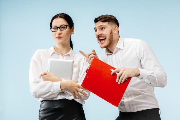 Concept van partnerschap in zaken. jonge gelukkige glimlachende man en vrouw die zich tegen blauwe achtergrond bij studio bevinden