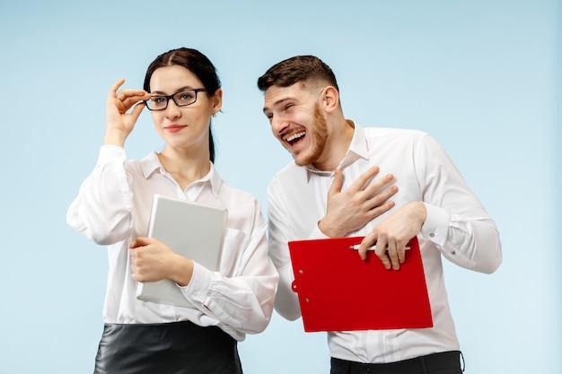 Concept van partnerschap in zaken. jonge gelukkige glimlachende man en vrouw die zich tegen blauwe muur bevinden