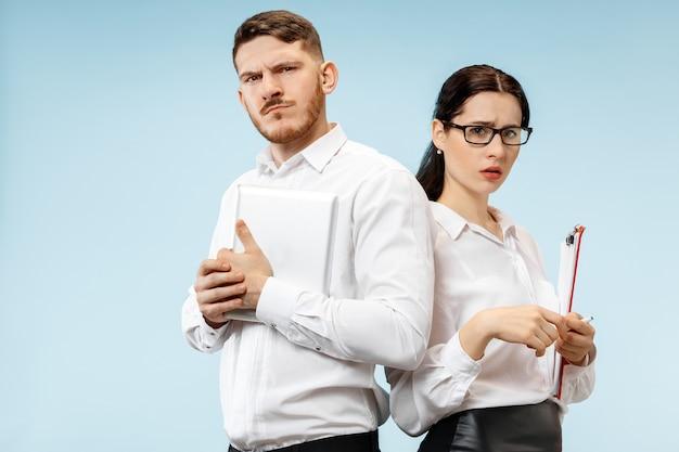 Concept van partnerschap in zaken. jonge man en vrouw die verdacht kijken tegen blauwe muur