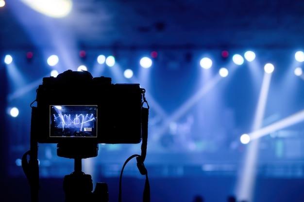 Concept van productie in pubs en concertevenementen, camera die stralen uit schijnwerpers schiet en lichten in blauwe tinten.