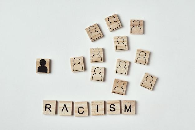 Concept van racisme en misverstand tussen mensen, vooroordelen en discriminatie. houten blok met een wit zwart figuur gescheiden van blanke mensen en woord racisme