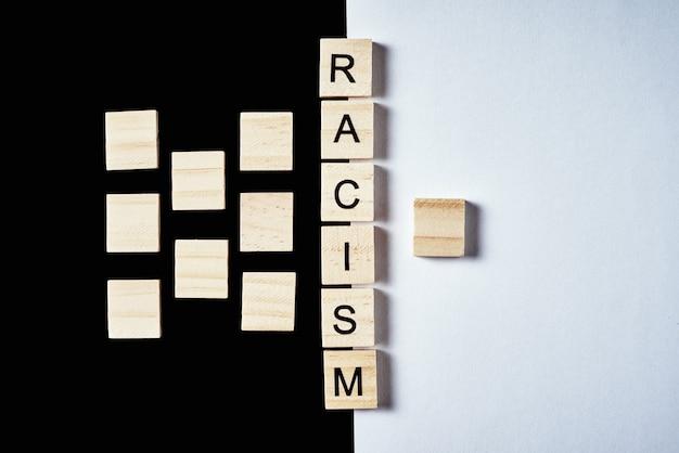 Concept van racisme en misverstanden tussen mensen, vooroordelen en discriminatie. veel houten blokken gescheiden van een met woord racisme