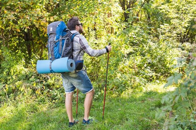 Concept van reizen, avonturen, wandelen, toerisme en natuur - toerist die in het bos loopt