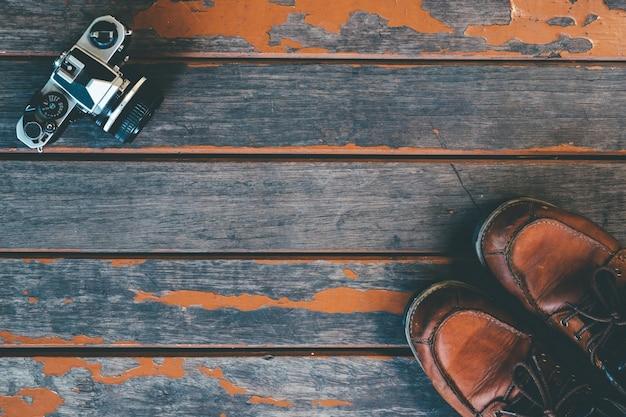 Concept van reizen en verkenner - oude vinatge camera en lederen laars op houten achtergrond