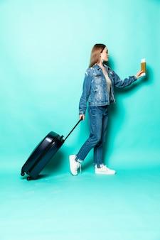 Concept van reizen. gelukkig vrouwenmeisje met koffer en paspoort op groen gekleurde muur