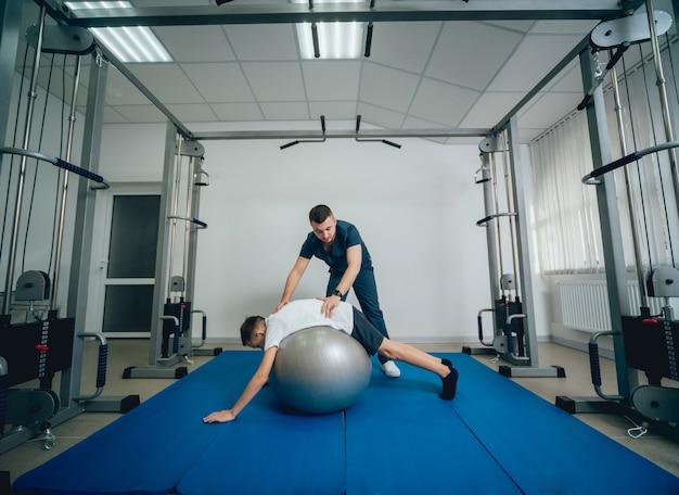 Concept van revalidatie. jonge jongen die oefeningen met bal doet onder toezicht van fysiotherapeut