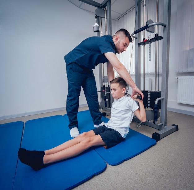 Concept van revalidatie. jonge jongen die oefeningen op mat doet onder toezicht van fysiotherapeut