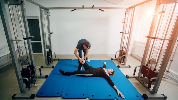 Concept van revalidatie. mooie jonge vrouw die oefeningen op mat doet onder toezicht van fysiotherapeut