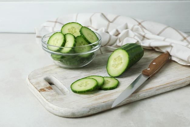 Concept van rijpe groente met komkommers op witte geweven lijst