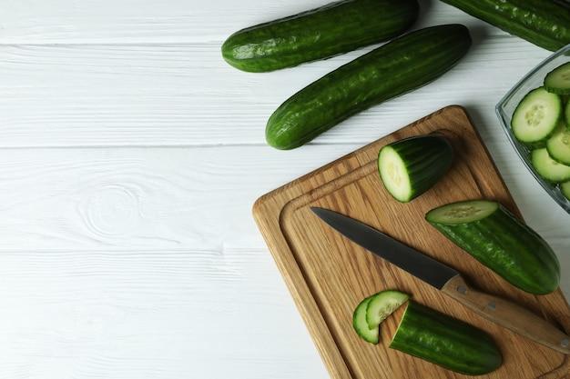 Concept van rijpe groente met komkommers op witte houten tafel