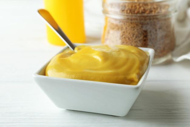 Concept van saus met mosterd op witte houten tafel