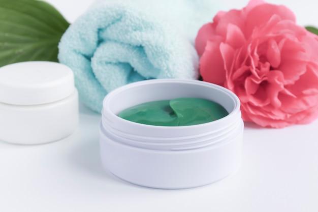 Concept van spa-behandelingen. hydrogel pleisters om de huid rond het oog, bloemen en handdoek te verzorgen en te hydrateren.