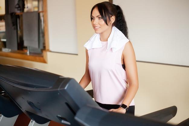 Concept van sport en een gezonde levensstijl. jonge aantrekkelijke fitness vrouw die op tredmolen loopt, die in witte sportkleding draagt. gezonde sportieve vrouw die cardiooefening op tredmolen doet
