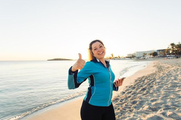 Concept van sport, fitness, gezonde levensstijl en hardlopen - gemotiveerde sportieve vrouw die een succesgebaar met duim omhoog doet na een training in de buitenlucht op het strand.