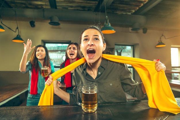 Concept van sport, mensen, vrije tijd, vriendschap, entertainment - gelukkige vrouwelijke voetbalfans of goede jonge vrienden die bier drinken, de overwinning vieren in de bar of pub. menselijke positieve emoties concept