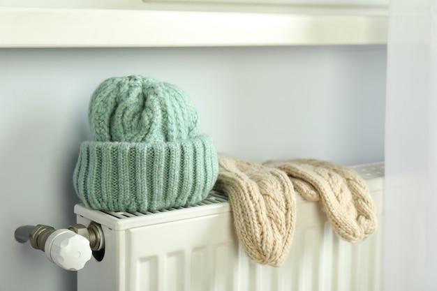 Concept van stookseizoen met gebreide kleding op radiator.