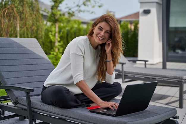 Concept van succes en freelance werk. volledige weergave van lachende zakenvrouw die aan een notebook werkt op een gezellig terras van haar villa. vrouw die smartphone vasthoudt en naar de camera glimlacht