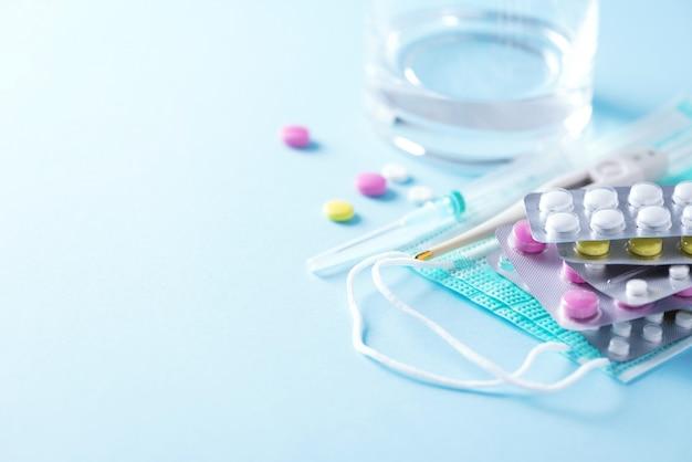 Concept van therapie, preventie van virusgriep, virale aanval, verkoudheidspillen, antibiotica en vitamines, beschermende medische gezichtsmaskers op blauwe achtergrond. coronavirus covid-19. kopieer ruimte