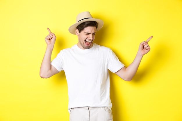 Concept van toerisme en levensstijl. gelukkig man genieten van vakantie, toeristische dansen op gele achtergrond.