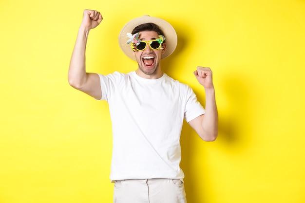 Concept van toerisme en levensstijl. gelukkige man die reis naar resort wint, ja schreeuwt en handen omhoog steekt, triomfeert, zonnebril en zomerhoed draagt, gele achtergrond.