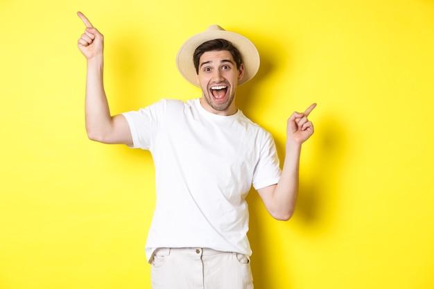 Concept van toerisme en levensstijl. gelukkige toerist die danst en met de vingers zijwaarts wijst, met vakantievarianten, gele achtergrond.