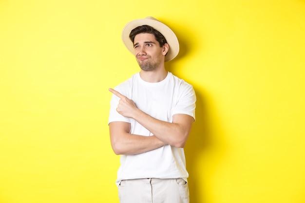 Concept van toerisme en levensstijl. ontevreden mannelijke toerist die met teleurstelling klaagt, kijkt en met vinger naar de promo in de linkerbovenhoek wijst, die zich tegen een gele achtergrond bevindt.